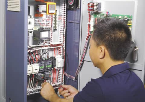 装配车间_职员在对模温机进行超温模块调试